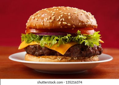 Homemade grilled hamburger on plate with red background