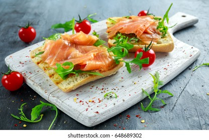 Homemade grilled toast with Smoked Salmon, rucola, tomatoes on white board. healthy breakfast
