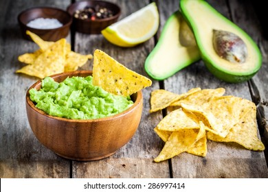 homemade guacamole with corn chips on rustic wooden table