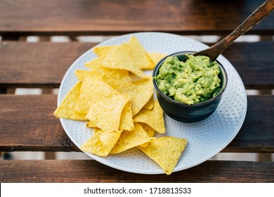 Homemade guacamole with corn chips tortillas on a wooden table - Traditional spicy Mexican preparation
