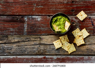 Homemade guacamole dip with chips on rustic wooden background. Food and vegetarian concept. Top view.