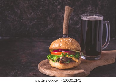 Homemade hamburger and beer on dark background with copy space