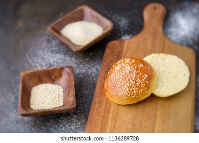 Homemade Hamburger Bun Topped with Sesame Seeds Cut Open on a Wood Cutting Board; Rustic Black Background; Cane Sugar and Sesame Seeds in Small Wood Bowls Beside; Flour Scattered on Background
