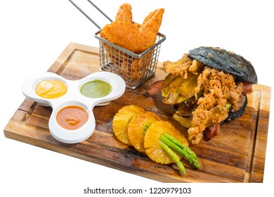 Homemade hamburger, Burger charcoal with Fried pumpkin, cheese, beef, meat,Asparagus sliced in pineapple and big french fries in small Cart placed served on wooden planks on isolated white background