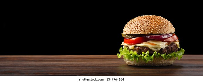 Homemade hamburger close-up with beef, tomato, lettuce, cheese and onion on wooden table. Fastfood on dark background with place for your text.