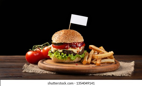 Homemade hamburger close-up with beef, tomato, lettuce, cheese and french fries on cutting board. Small white flag inserted in the burger. Fastfood on dark background.