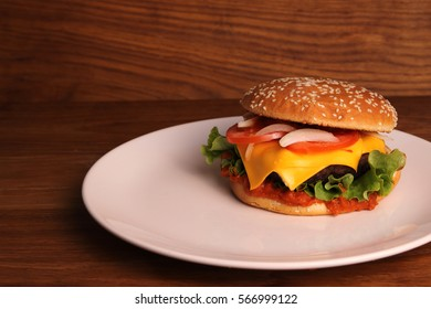 Homemade hamburger with double cheese, tomatoes, onions and on a wooden table  in a white plate, unhealthy food.
