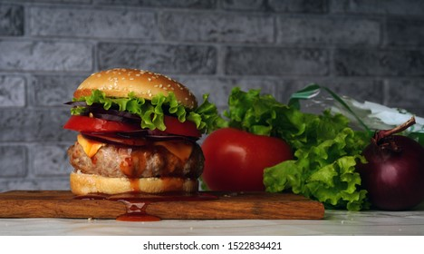 Homemade hamburger with fresh vegetables. Tasty grilled burger with with beef, cheese, vegetables. Delicious grilled Cheeseburger. Free space for text