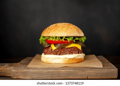 Homemade hamburger with lettuce, tomato, cheese and cucumber on a cutting board