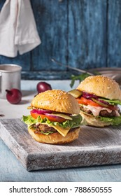 Homemade hamburgers with beef, cheese and vegetables on rustic table. Closeup