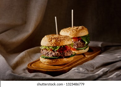 homemade hamburgers with beef cutlet with tomatoes and salad on a wooden board at home with a beautiful light
