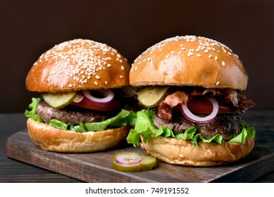 Homemade hamburgers with beef, fried bacon, onion, tomato, lettuce and marinated cucumber on wooden board. Close up view