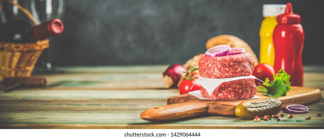 Homemade hamburgers. Raw beef patties and ciabatta bread with other ingredients for hamburgers on wooden background