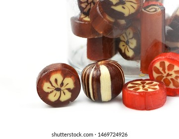 homemade hard sugar candy,boiled sweet with small glass jar as background isolated on white