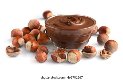 Homemade hazelnut spread in glass bowl with nuts isolated on a white