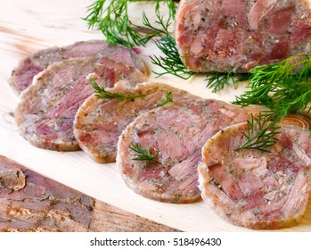 Homemade headcheese with dill and cranberries on a wooden board