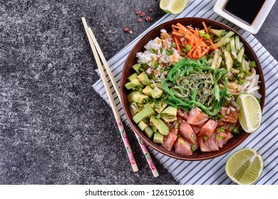 Homemade healthy Poké bowl with rice, salmon, avocado, white onion, scallion greens, sesame oil, soy and sesame sauce, seaweed (wakame) and other ingredients on a dark backgound are ready to eat