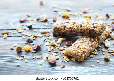 Homemade healthy cereal bars with granola, nuts and dried fruits on wooden background.