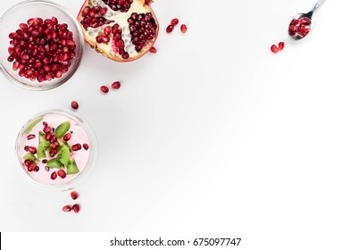 Homemade healthy chia seeds pudding with almond milk, berries yogurt, pomegranate and kiwi served in a glass on white background. Overhead, top view, flat lay. Copy space