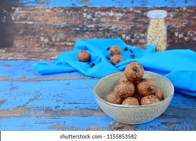 Homemade healthy energy balls with chocolate, raisin, quinoa and oat on blue background