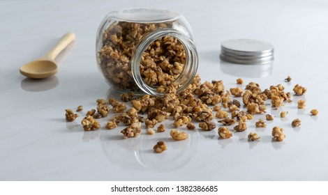 Homemade healthy and nutritious breakfast granola in a glass jar with wood spoon on clean white marble kitchen table in fresh morning light