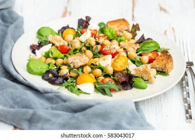 Homemade Healthy Salad made from Rocket Salad, Basil, Cherry Tomatoes, Chickpeas, Mozzarella, Sesame on Light Background