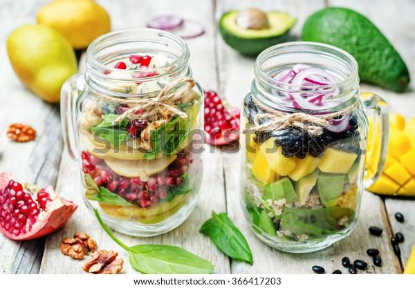 ensaladas caseras saludables con verduras, frutas, frijoles y quinua en frasco. tonificante. enfoque selectivo
