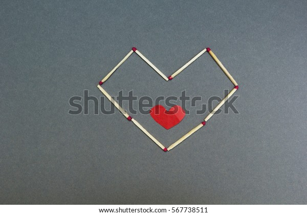 Homemade heart of matches on a gray background.