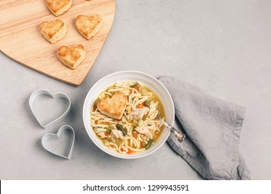 Homemade Heart-shaped Biscuits served with Homemade Chicken Soup on Gray Background