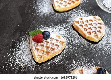 Homemade heart-shaped waffles dusted with icing sugar lie on a dark marble surface - delicious waffles for breakfast or coffee in the afternoon - freshly baked and golden brown