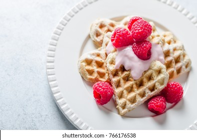 Homemade heart-shaped waffles with raspberries and  redcurrant on a white plate and light-blue stone background