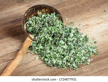 Homemade herbal salt from various herbs on the spoon. It contains cut wild garlic, oregano, rosemary and lavender flower with sea salt.