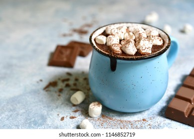 Homemade hot chocolate with mini marshmallow in a blue enamel mug on a light slate background.Rustic style.