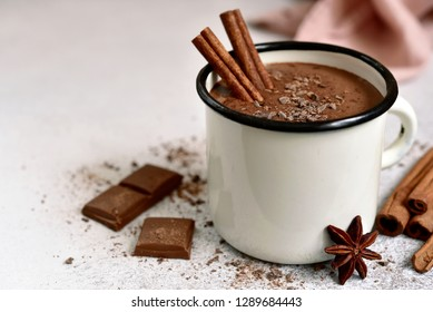 Homemade hot chocolate in a white enamel mug on a light slate, stone or concrete background.
