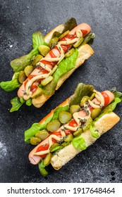 Homemade hot dogs with vegetables, lettuce and condiments. Black background. Top view