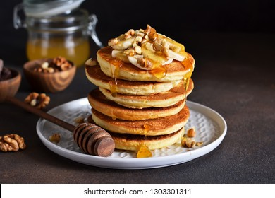 Homemade, hot pancakes with banana, honey and nuts on the kitchen table.