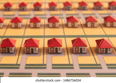 Homemade houses with red roofs made of paper. Selective focus, blurred background. Close-up, macro. Abstract model of a village or city district. The project of a new neighborhood or a DIY game.
