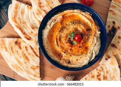Homemade hummus with pita bread on a dark table. Selective focus and small depth of field.