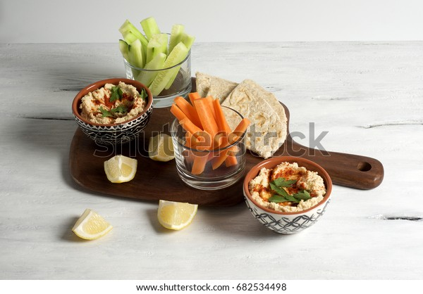 Homemade hummus with pita, carrot and cucumber sticks