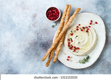 Homemade hummus with pomegranate, thyme, olive oil and pine nuts with grissini bread sticks. Middle Eastern traditional and authentic arab cuisine. Top view, flat lay, overhead