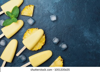 Homemade ice cream or popsicles from pineapple decorated with mint leaf. Top view. Frozen fruit pulp. Summer sweets.
