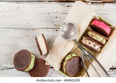 Homemade ice cream sandwich with chocolate cookies whoopie pie. With berry, vanilla and mint ice cream, supplemented with chocolate chips. On a white wooden table. Copy space top view
