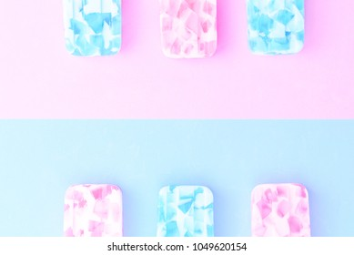 Homemade Ice cream sticks , popsicle , ice pop or freezer pop on blue and pink pastel colors background