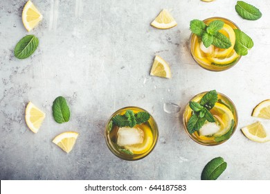 Homemade iced lemon sweet tea with mint on light gray table with copy space viewed from above, delicious refreshment summer drink