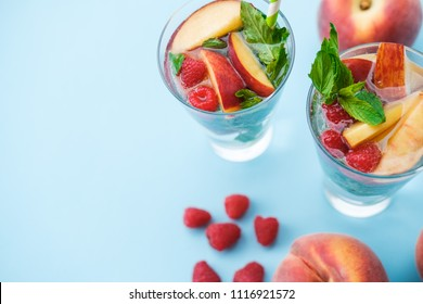 Homemade iced lemonade or tea with ripe peaches and Raspberries. Blue background. Top view