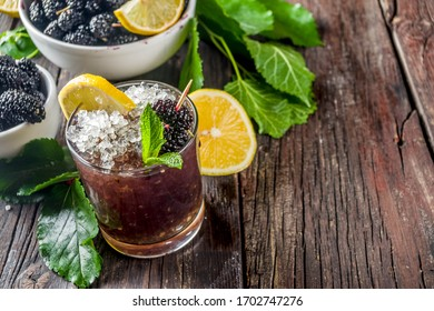 Homemade iced mulberry lemonade or mojito cocktail, with fresh mulberries, lemon slices and mint, rustic wooden background copy space