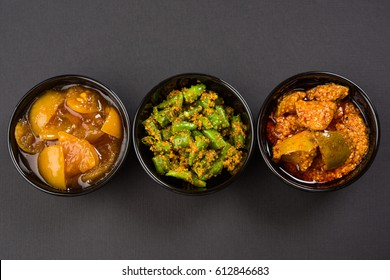 Homemade Indian Pickles of Red/Green Chilli, Mango and Lemon, also known as Mirchi, Aam and Nimbu ka achar Served in ceramic bowls, selective focus