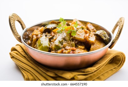 Homemade Indian spicy eggplant and potato curry also known as aloo Baigan ki sabzi in hindi, served in kadhai or white bowl, selective focus