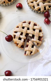 Homemade individual Lattice Cherry pie. Simple, delicious patisserie, home rustic baking, summer french dessert concept. Top view, flat lay, Copy space