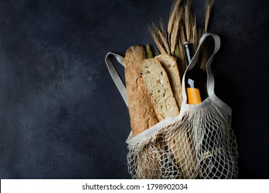 Homemade Italian bread baguette stirato and a bottle of wine in a shopping bag